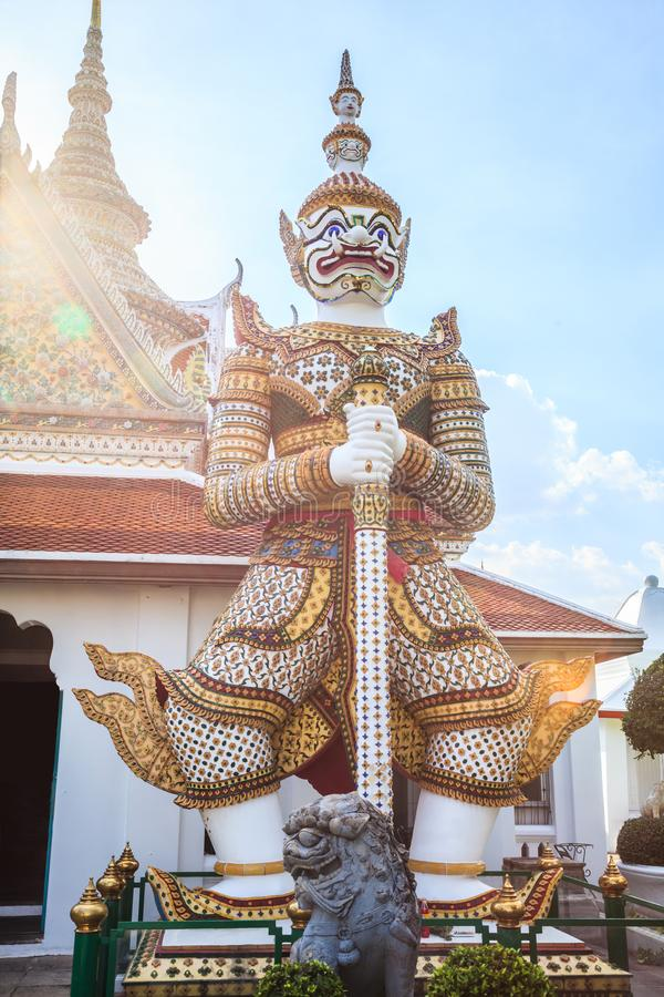 Ancient temple guardian in front of Temple of Dawn Wat Arun Buddhist Temple is white demon giant statue named Sahatsadecha. stock images