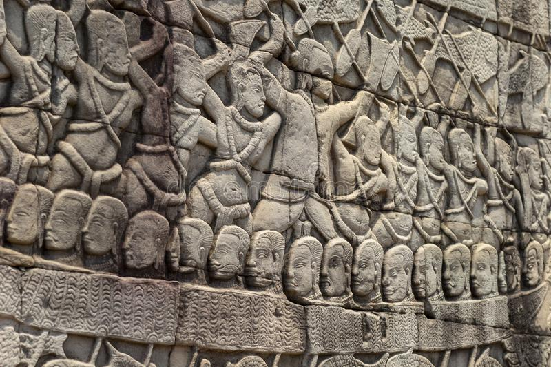 Ancient temple stone carved bas-relief in Angkor Wat. Army in boat bas-relief closeup. Angkor Wat complex Bayon temple royalty free stock image