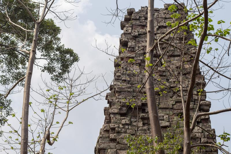 Ancient temple view near Angkor Wat, Siem Reap, Cambodia. Distressed stone tower with tree. Popular tourism destination place. Travel and sightseeing in Angkor stock photos