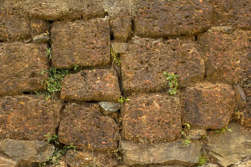 A ancient terracotta wall of stone bricks of different sizes with dry and green grass. natural rough surface texture stock photos