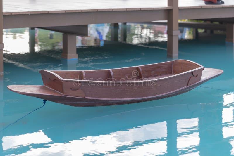 Fake ancient Thai wooden boat on blue lake. Ancient Thai wooden boat on blue lake royalty free stock photos