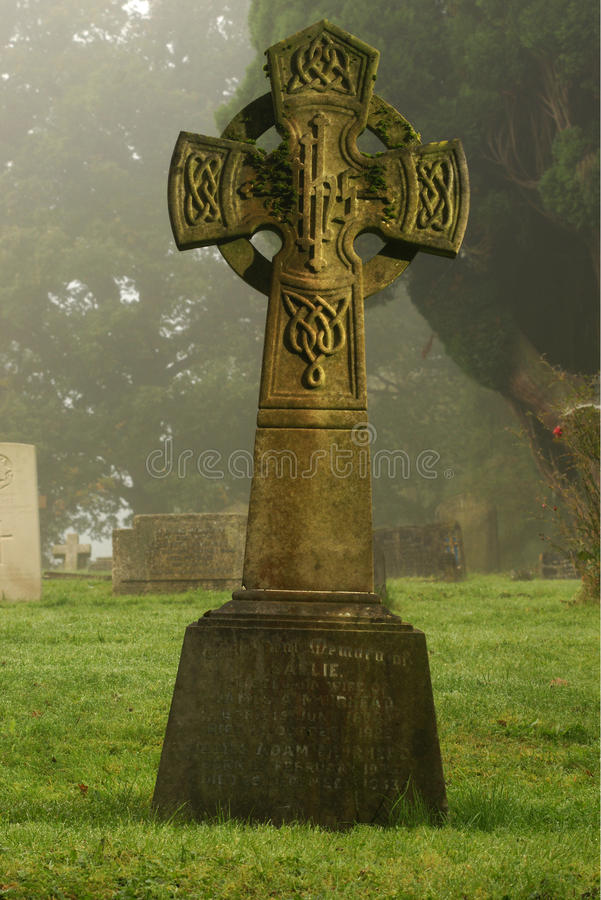 Ancient tomb in misty graveyard on cold morning stock photography