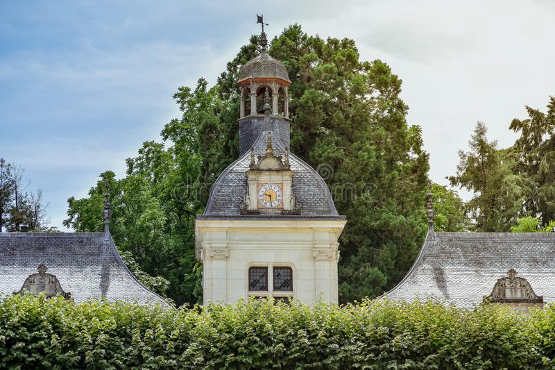 Ancient tower clock between the foliage on a sunny day. France stock images