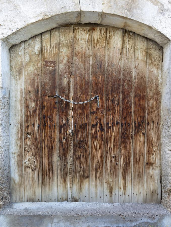 Ancient trapezoidal antique wooden doors with a metal lock in the middle stock images