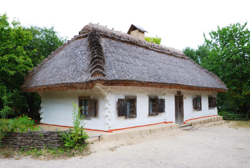 Ancient Ukrainian house thatched. Vintage house is made in Ukrainian folk style of 17th century. There is the white building with thatch stock photo
