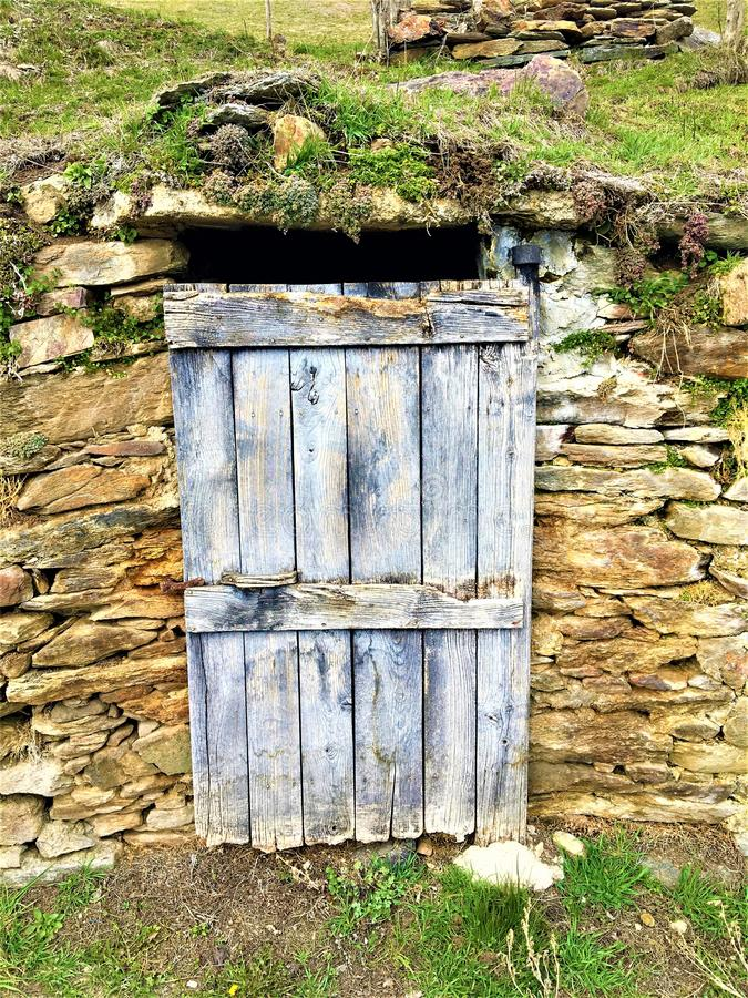 Ancient and vintage blue door, stones and nature. Artistic and historical details, secret hole, mystery, craftsmanship, enchanting and peculiar location royalty free stock photos
