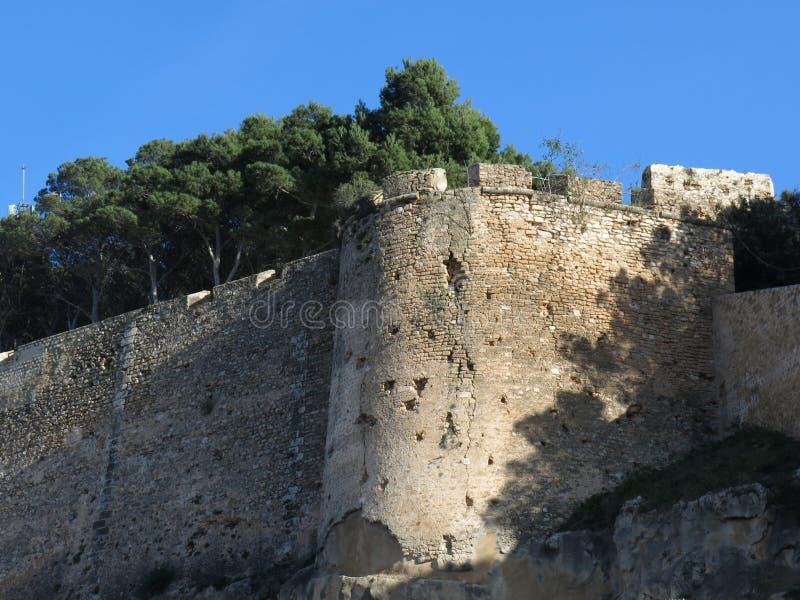 Ancient wall surrounding the Castillo de Denia, Spain. Corner of the ancient wall surrounding the Castillo de Denia, Spain royalty free stock photos