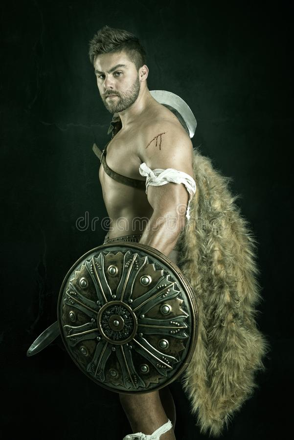 Gladiator/Warrior. Ancient warrior or Gladiator posing over a dark background stock images