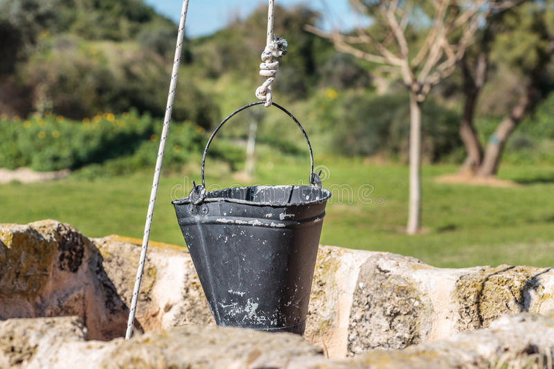 Ancient water well with a bucket. A stone pit stock photography