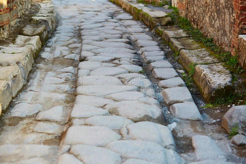 Ancient wheel track in Pompeii, Italy. Ancient wheel track in Pompeii, Roman town near modern Naples destroyed and buried under volcanic ash during eruption of stock photography