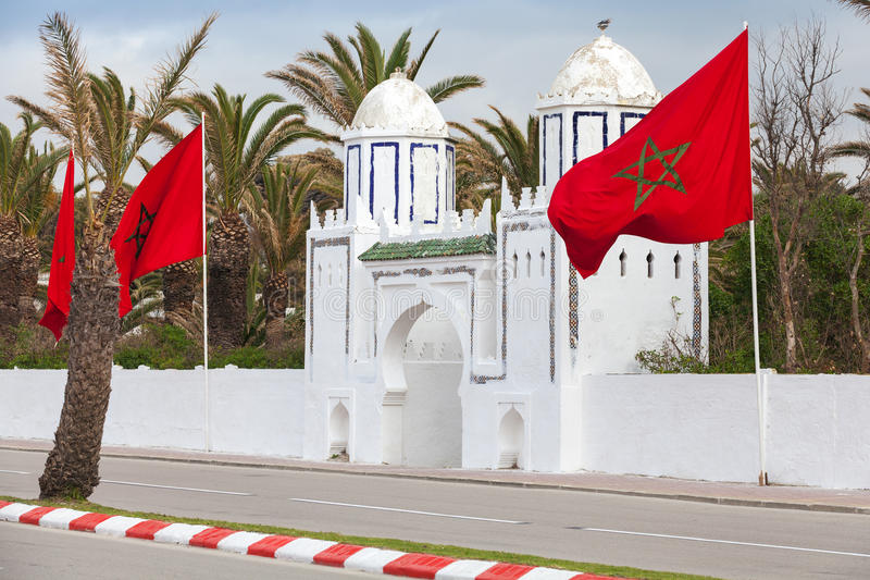 Ancient white gate to the park in Tangier, Morocco. Ancient white gate to the park and flags in Tangier, Morocco stock images