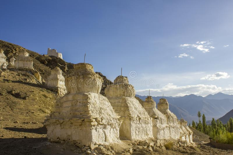 A ancient white holy Tibetan Buddhist temples on a desert mountain in the daytime against the backdrop of a mountain valley. Ancient white holy Tibetan Buddhist stock photo