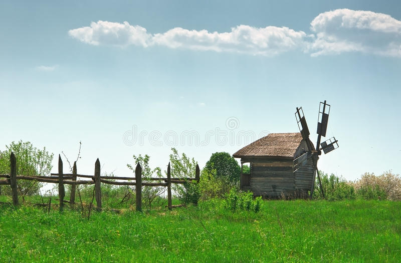 Ancient windmill in field stock photo