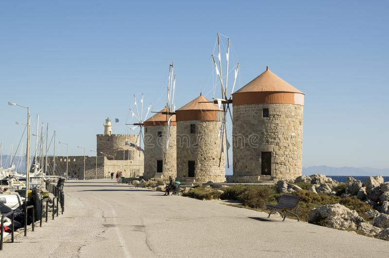 Ancient windmills on stony Rhodes coastline in harbor, old historic buildings, place of interest, blue sky stock photos