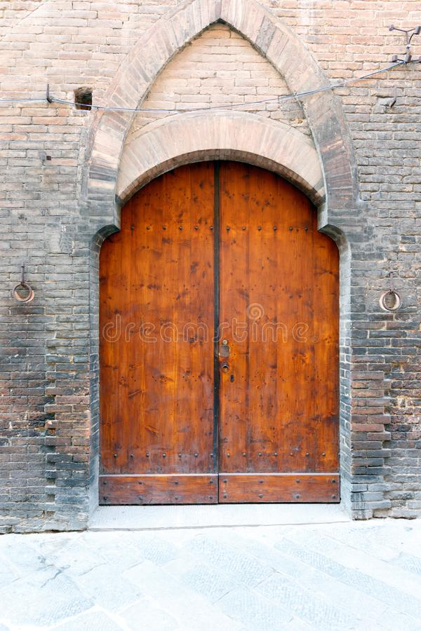 Ancient wooded double doors in a brick wall with decorative arch stock images