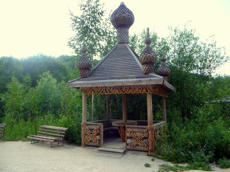 Ancient wooden alcove in an ethnographic park. A carved wooden pergola in the Slavic ethnographic park royalty free stock photography