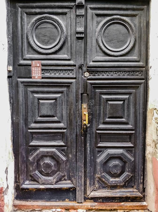 ancient wooden black doors with infill and door handle stock photo