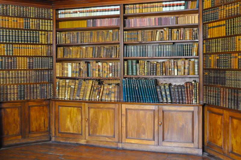 Ancient wooden book shelves with old library books Dusty bookshelf with rare books collection in bookcase Retro library royalty free stock photography