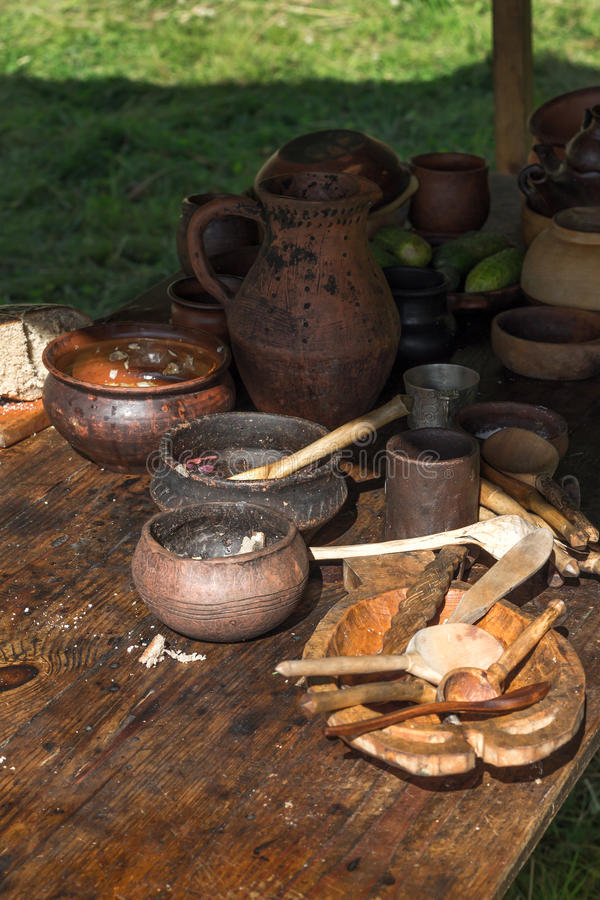 Ancient wooden and clay dishes left on table after dinner royalty free stock photography