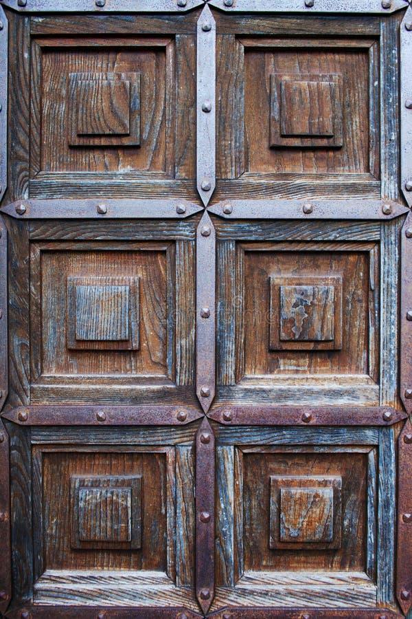Ancient wooden door. Ancient wooden church door with metallic edges royalty free stock photography