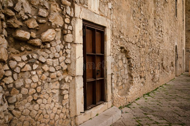 Ancient wooden door in the brick wall of italian castle. Medieval architecture concept stock photo