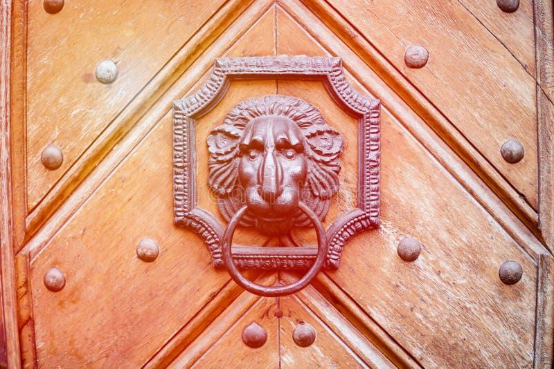 An ancient wooden door with door knocker in the shape of a lion. Orange toned stock photo