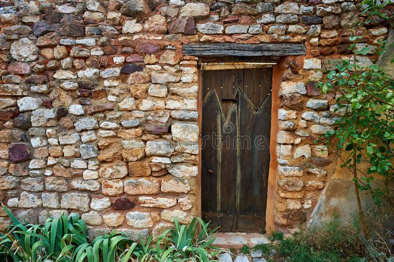 Ancient wooden door in a red ochre stone wall stock photos