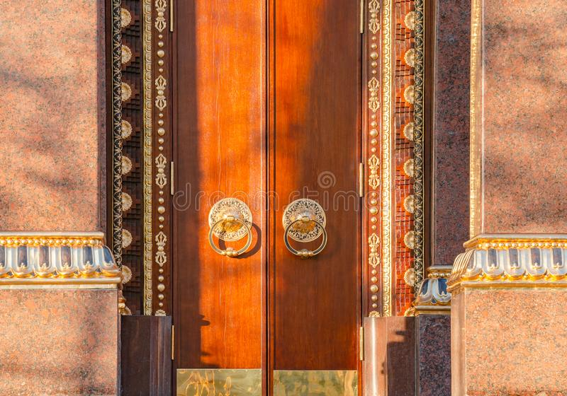 Ancient wooden gate with two golden door knocker rings close-up front view. Old Door Fragment of Buddhist temple Datsan royalty free stock images