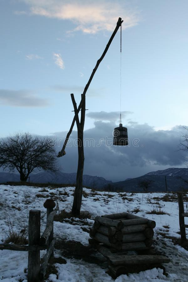 Ancient wooden pendulum type well in winter evening royalty free stock photography