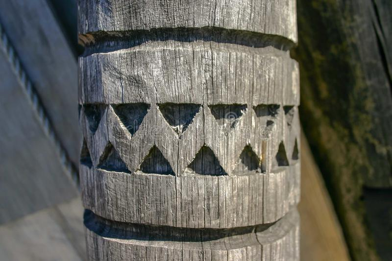 An ancient wooden pillar with a carved pattern. royalty free stock image
