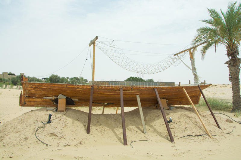 Ancient wooden small ship on the sand in the desert. In UAE stock images