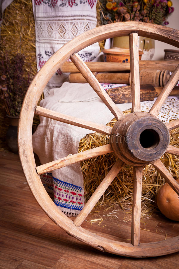 Ancient wooden wheel in the interior. Ancient wooden wheel as the decor in the interior stock photo