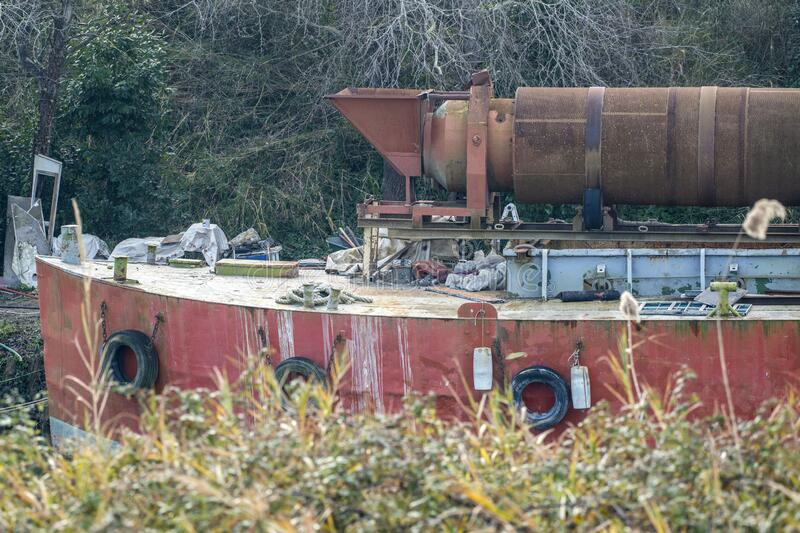 Ancient work boat. On a riverside by a sunny winter day in Italy royalty free stock photography