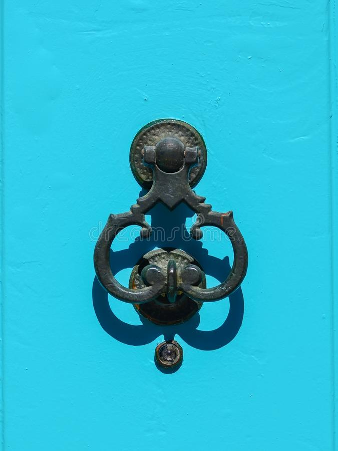 Ancient wrought iron door knocker on a blue background. stock photos