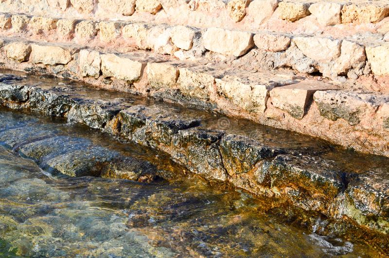 Ancient yellow stone steps of cobblestones covered with green mud and mud, descent into the sea, a lake, an ocean and water with w royalty free stock photo