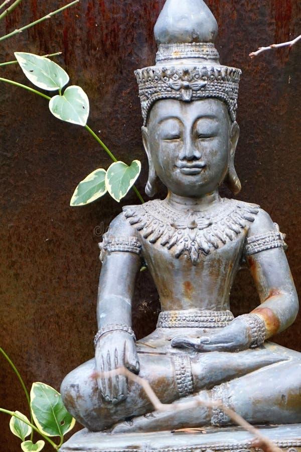 Ancient zittend Boeddha-standbeeld met gesloten ogen omgeven door groene bladeren stock afbeeldingen