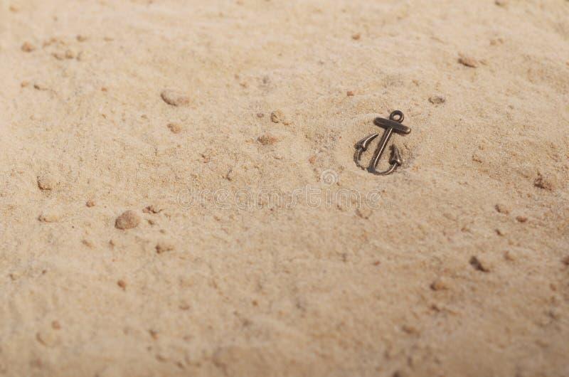 Ancla de bronce en la arena amarilla imágenes de archivo libres de regalías