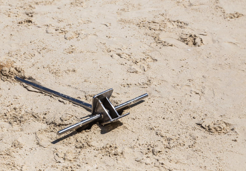 Ancla del acero inoxidable en la arena imagen de archivo libre de regalías