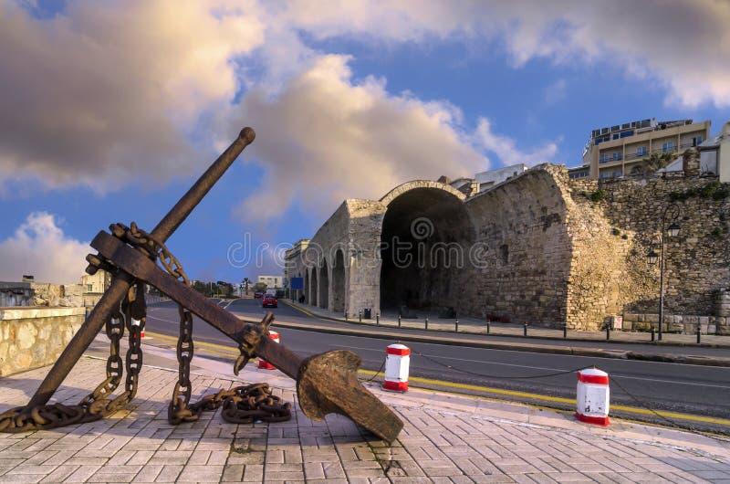 Ancla oxidada grande vieja y los astilleros venecianos viejos en el camino costero de Heraklion imagen de archivo