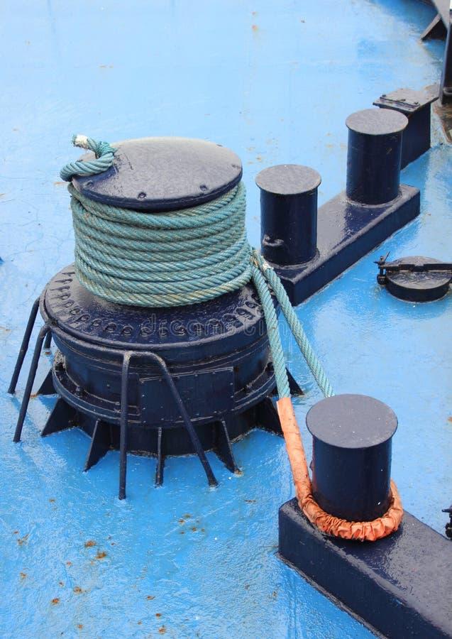 Ancle el torno con la cuerda en cubierta azul de la nave foto de archivo