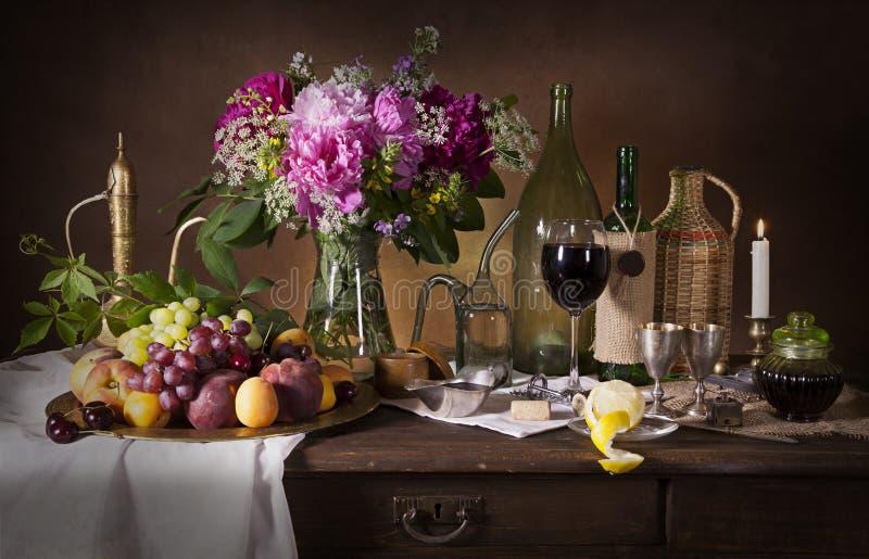 Ancora vita con i fiori ed il vino fotografia stock
