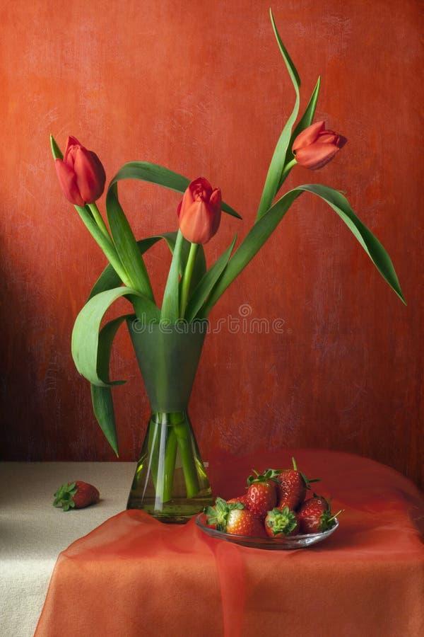 Ancora vita con i tulipani e le fragole immagine stock