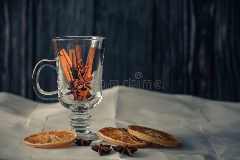 Ancora vita con le spezie cannella e anice stellato in una tazza di vetro trasparente con le fette secche del pompelmo su carta e immagini stock libere da diritti