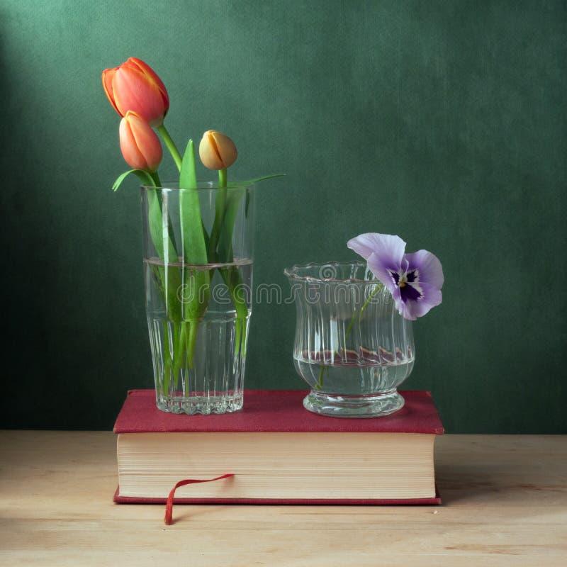 Ancora vita con vetro con i tulipani e vetro con P fotografia stock libera da diritti