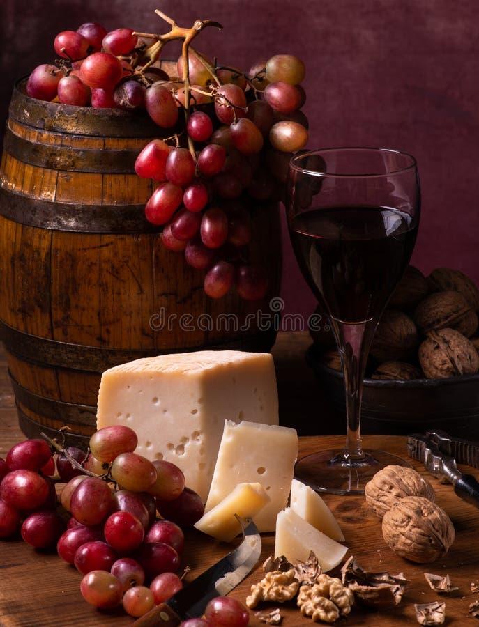 Ancora vita 1 formaggio di capra, uva, noci e vino rosso fotografia stock libera da diritti