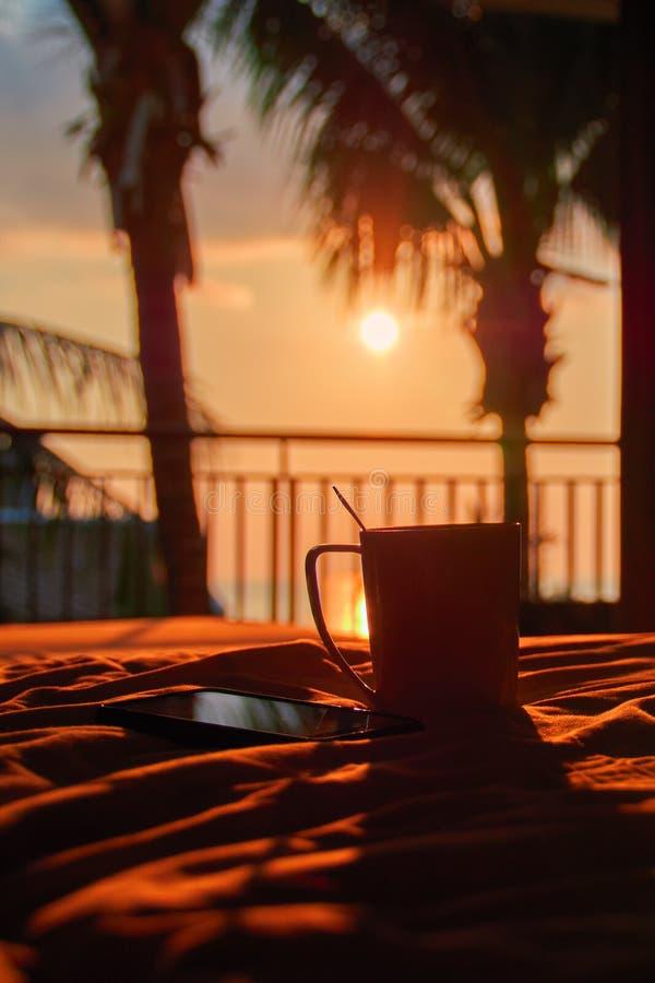 Ancora vita 1 Smartphone e tazza sul letto in mezzo del tramonto di sera e delle palme delle siluette Luce arancio calda Crepusco fotografie stock libere da diritti