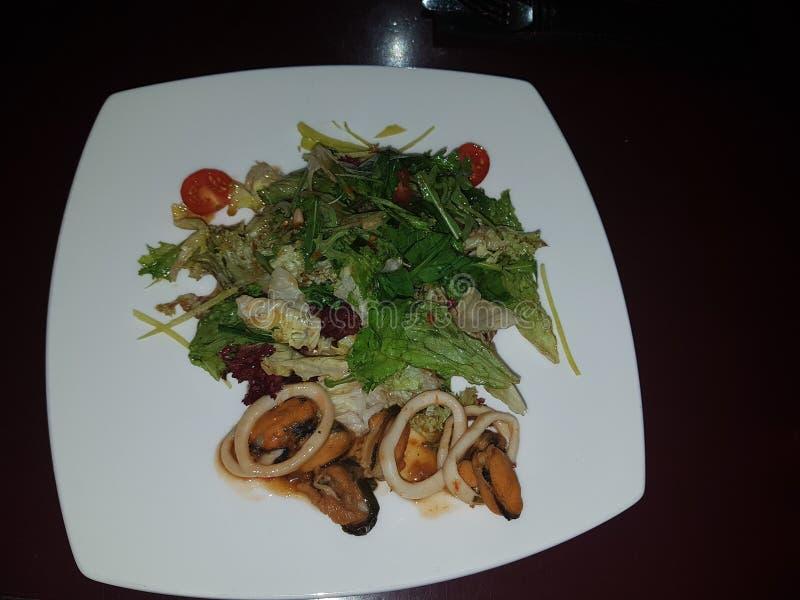Ancora vita 1 Su un piatto bianco con un'insalata Da un lato del piatto sono le cozze e i rapans, pomodori nella parte anteriore, immagini stock