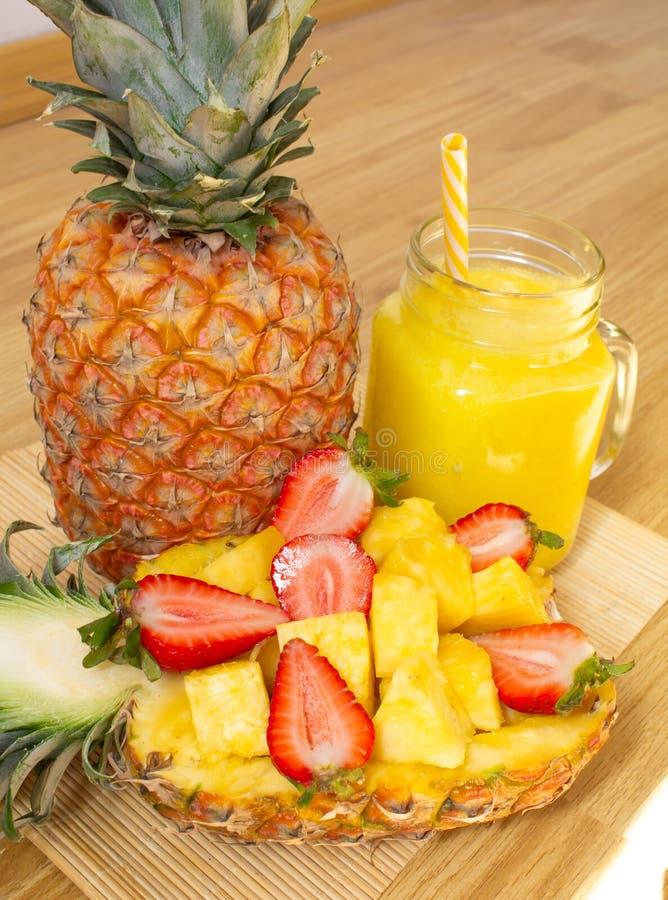 Ancora vita 1 Succo di ananas, cocktail con l'ananas fresco e fragole fresche per la prima colazione di mattina, su una tavola di immagini stock libere da diritti