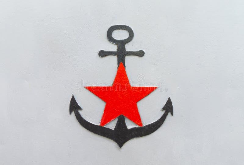 Ancrage noir avec étoile rouge sur fond de fer gris photographie stock