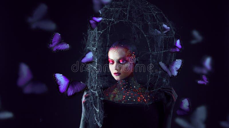 Andaavbrott frigör från buren Ung attraktiv flicka i ljus konst-makeup, många fjärilar arkivfoton